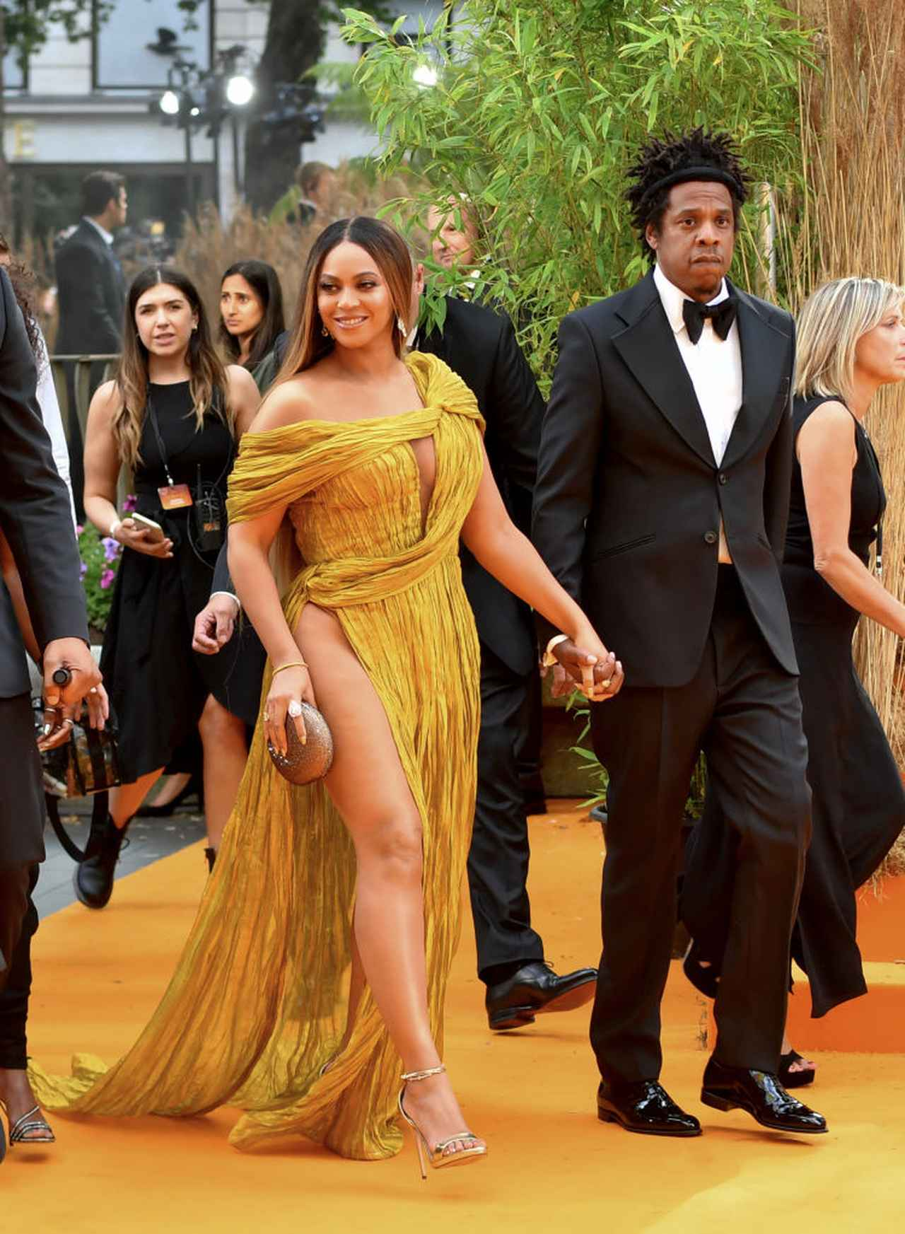 画像: レッドカーペットに登場したビヨンセ&ジェイ夫妻。ビヨンセはイエローカーペットに合わせてイエローゴールドのドレスをチョイス。