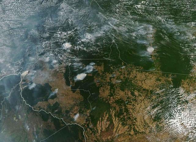 画像: アメリカ航空宇宙局(NASA)が公開した衛星写真。全体を白く覆っているのは火災によって発生した煙。 ©NASA