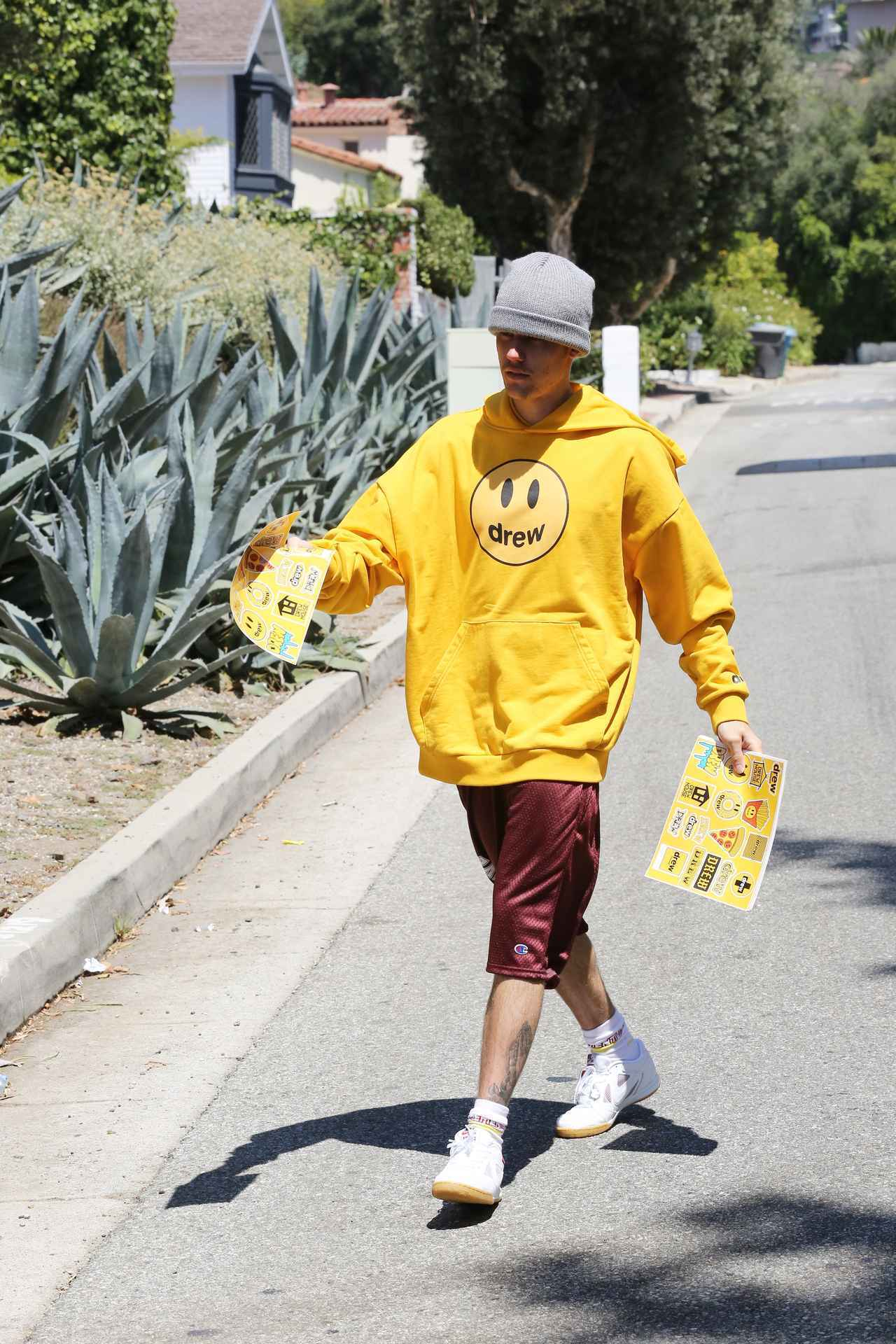 画像: 道行く人にステッカーを配ってブランドの宣伝をするジャスティン。