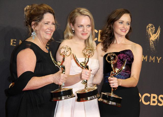 画像: 2017年度エミー賞で主人公ジューン役のエリザベス・モス(中央)とエミリー役のアレクシス・ブレデル(右)と揃ってエミー賞を受賞したリディアおば役のアン・ダウド(左)。