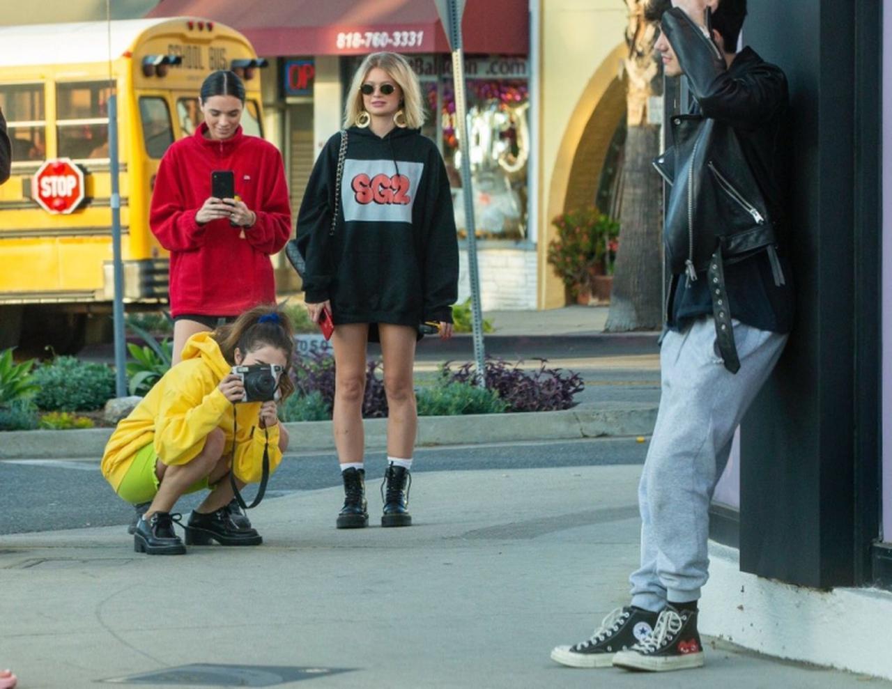 画像: 写真撮影中のセレーナを撮影するコナー、その隣がナタリー、アーロンは建物に寄りかかってクールにポーズ。 twitter.com