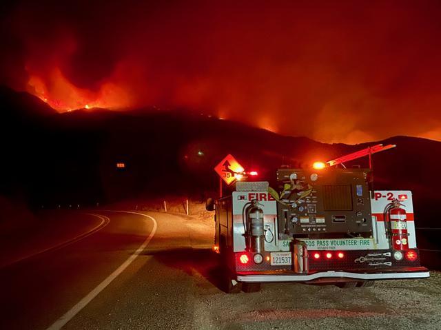 画像: 11月25日にカリフォルニア州サンタバーバラで発生した山火事の消火活動にあたる消防車。26日の時点で4200エーカー(約17平方キロメートル)を超える面積に延焼した。