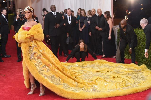 画像: メットガラの歴史に残る、ドラマティックなイエローのグオ・ペイ(Guo Pei)のドレスは制作に約2年の月日が費やされ、長さは4.8メートルにも及び、総重量は約25kg。当時無名のデザイナーであったグオ・ペイの作品を、リアーナが自らネットで見つけたことを告白して話題に。