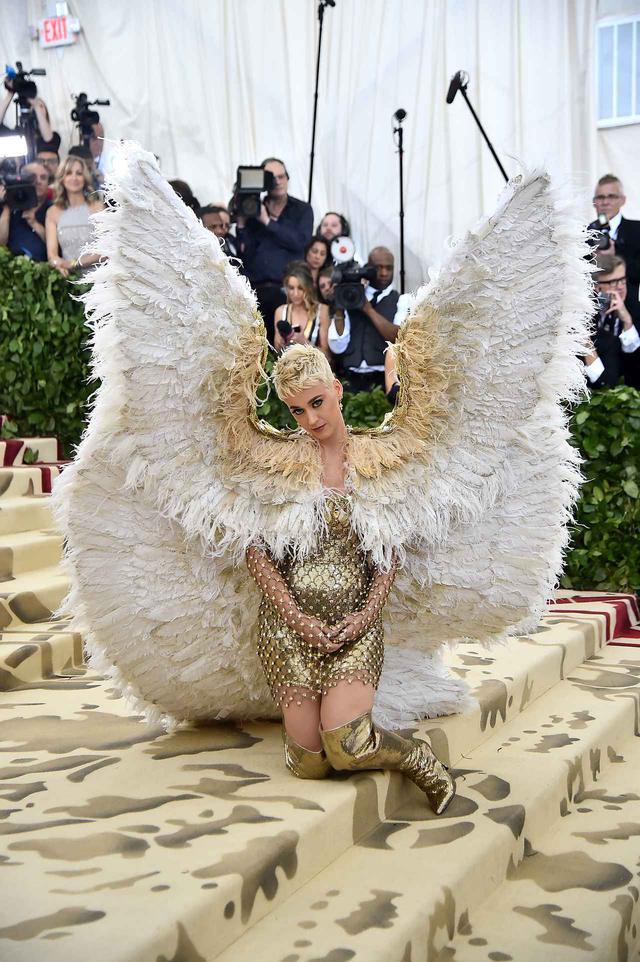 画像: ケイティ・ペリーは、この年のメットガラの「ヘヴンリーボディ:ファッションとカトリックのイマジネーション」というテーマにぴったりな天使のスタイルで登場。このゴージャスすぎる天使の羽がまわりにぶつかってしまい、知らず知らずのうちにそばにいたセレブを攻撃するシーンも。