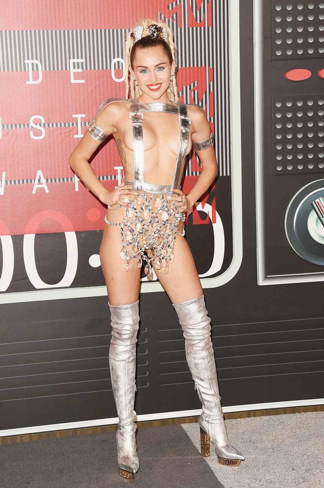 画像: この年MTV VMAで司会を務めたマイリーは、ほぼ全裸のドレスで登場。そのほかにもアワードでは、「DO IT」のバルーンがつけられたドレスや、超ハイレグの水着など、度肝を抜くような計10着もの衣装を着用した。