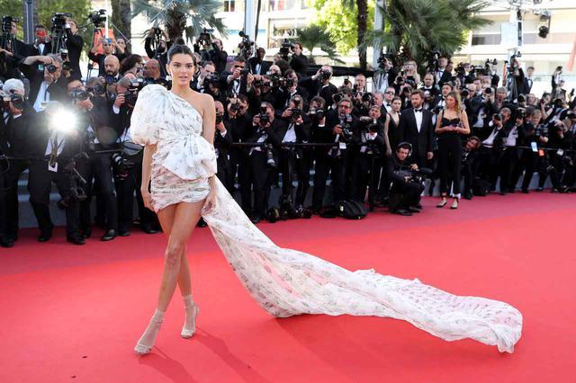 画像: ジャンヴァティスタ・ヴァリ(Giambattista Valli)のクチュールラインのドレスを着用し、地中海に面するカンヌの風をうけてトレーンをなびかせたドレス姿が絶賛されたケンダル・ジェンナー。足元にはヒールにウォルフォードのシアーなショートソックスをあえて合わせた、旬な着こなしも話題に。