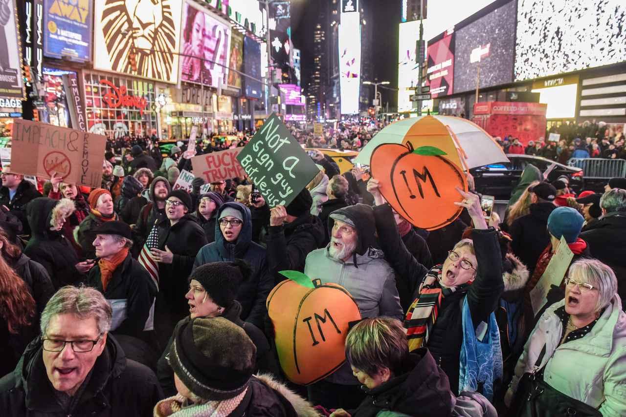 画像: 下院での弾劾審議の前夜には、全米でトランプ大統領の弾劾を求める集会が行なわれた。NYタイムズスクエア。