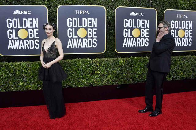 画像: ゴールデン・グローブ賞のレッドカーペットでカメラマンに向けポーズを決めるルーニーを恋する乙女のような表情で見つめる姿も話題になったホアキン。