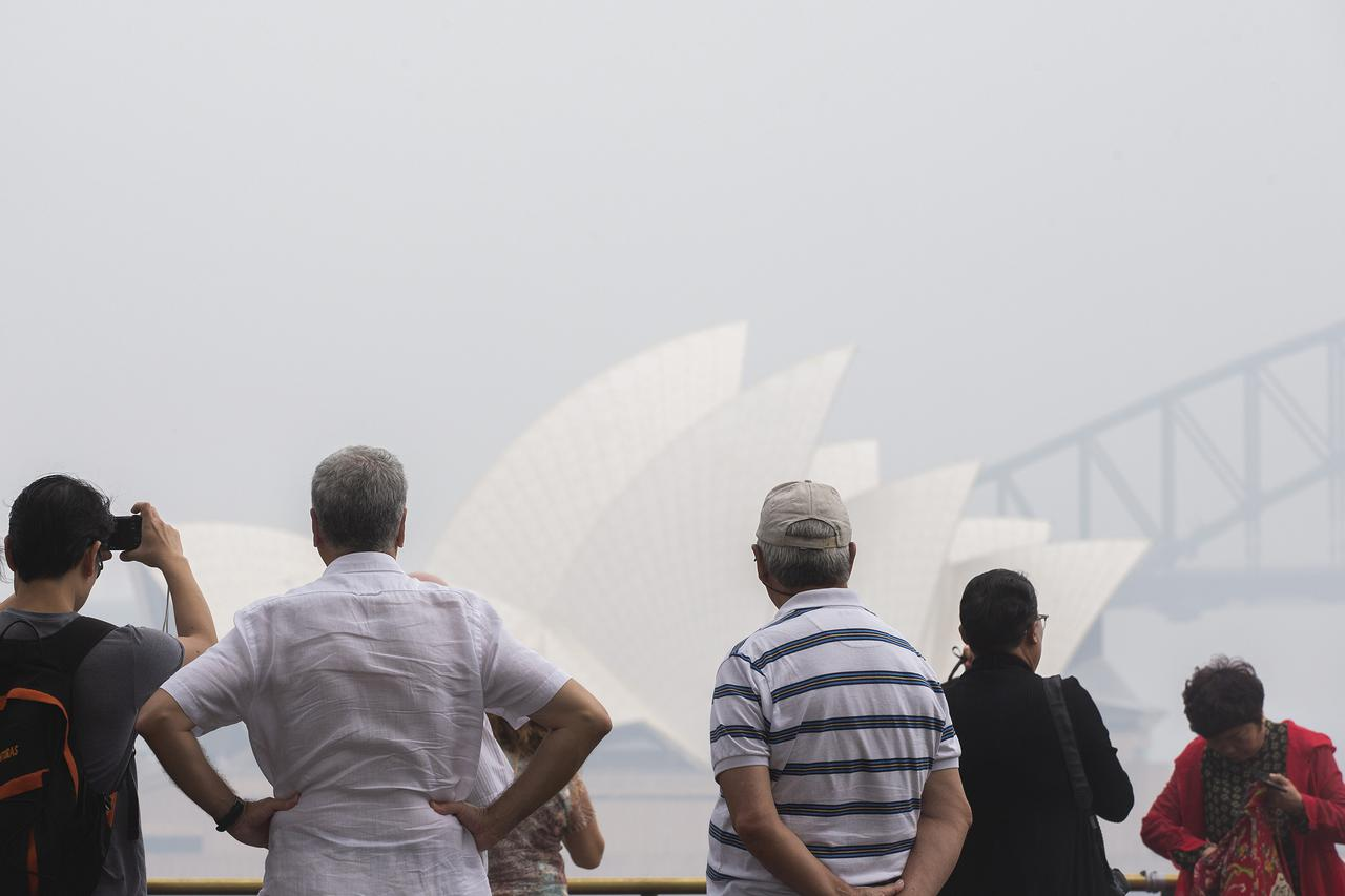 画像: 山火事の影響でオーストラリア各地の空は煙で覆われ、有害性が心配されている(シドニーのオペラ座前にて2020年1月8日に撮影)