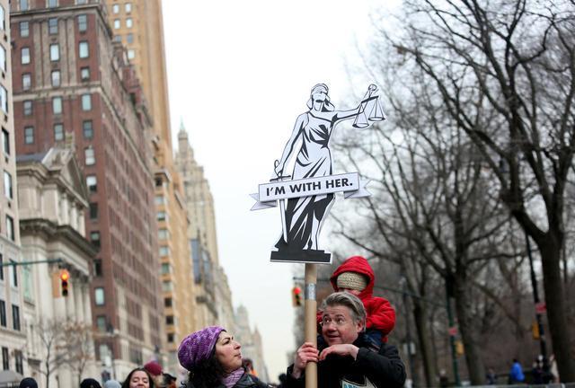 画像: 「I'M WITH HER(自分は彼女の味方)」というプラカードを掲げる男性。
