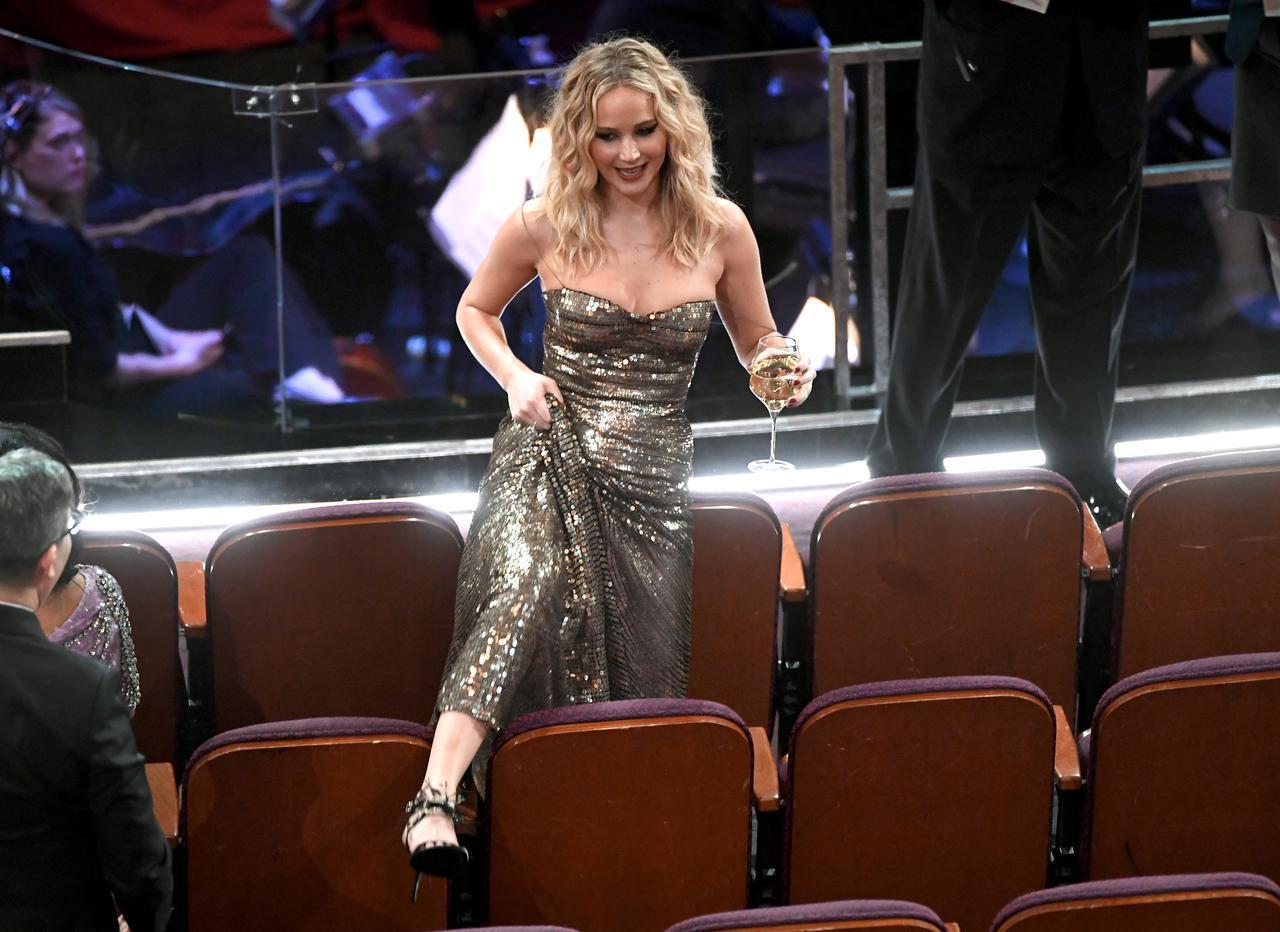 画像: 2018年のアカデミー賞授賞式開催中の様子。ご覧の通り、ジェニファー・ローレンスがシートをまたぐことが出来るほど、席に座っている人はほとんどいない。