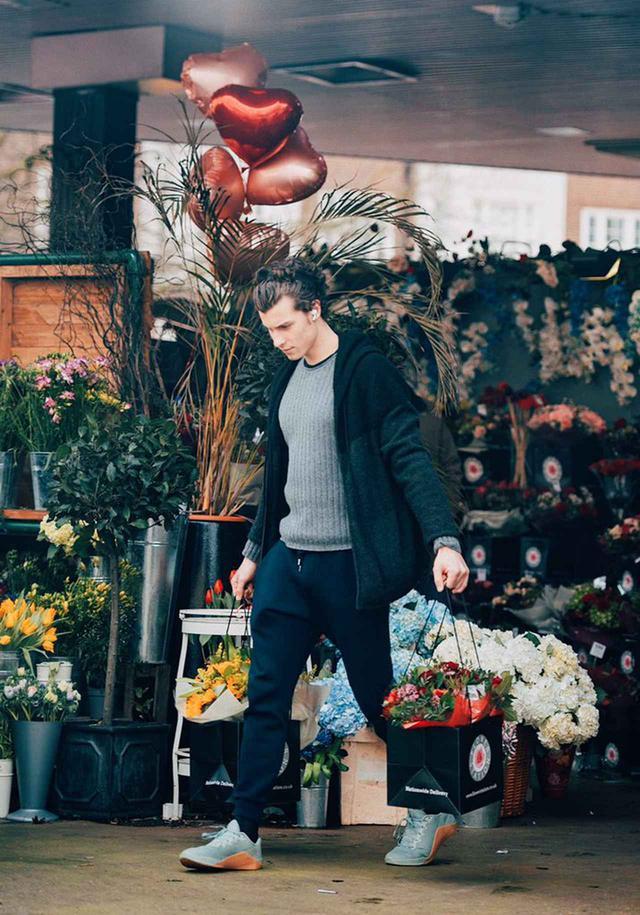 画像: 花束が入った紙袋を両手に持って花屋から出てくるショーン。