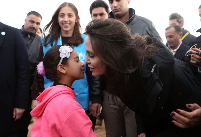 画像: 2018年にヨルダンにあるザータリ難民キャンプを訪れ、シリア難民の少女と話をするアンジェリーナ・ジョリー。