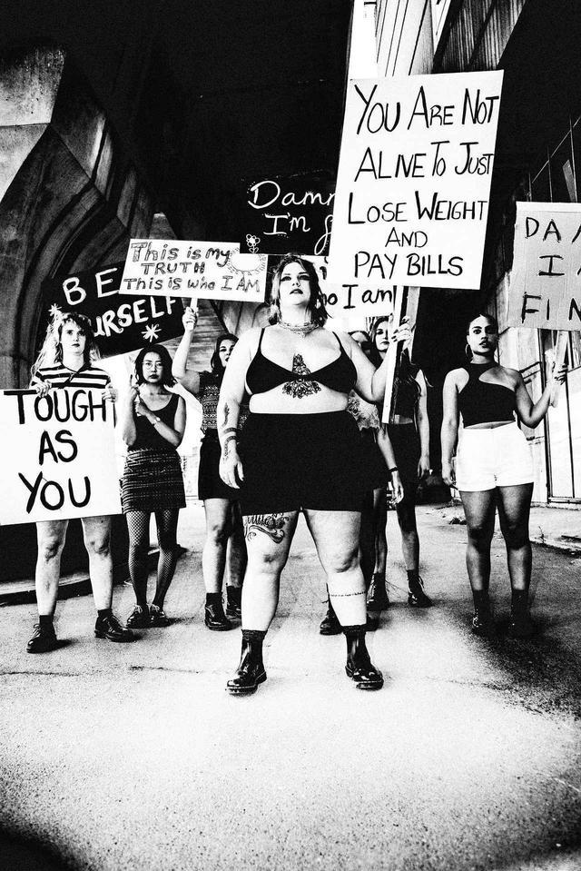画像: ドクターマーチンのブーツを履き、「あなたはただ体重を減らして、生活費を稼ぐために生きているわけじゃない」と書いたたプラカートを持ってメッセージを放つロッテ・ファン・エイク。