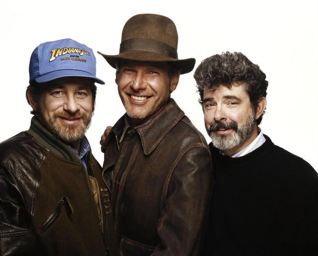 画像: シリーズ第3弾『インディ・ジョーンズ/最後の聖戦』が公開されたのと同じ1989年に撮影されたスリーショット写真。左からスティーヴン・スピルバーグ、ハリソン・フォード、ジョージ・ルーカス。