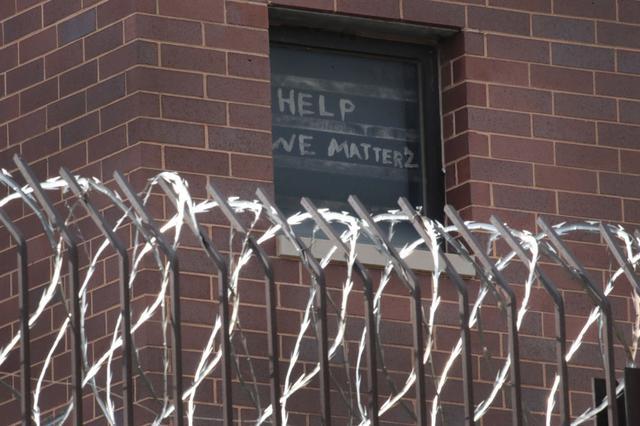 画像: イリノイ州シカゴにあるクック郡刑務所の窓には囚人たちが貼り出した「助けて、私たちだって重要だ」との悲痛なメッセージが。