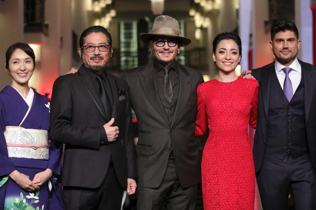 画像: ジョニーの右側にいる赤いドレスを着た女性が美波。