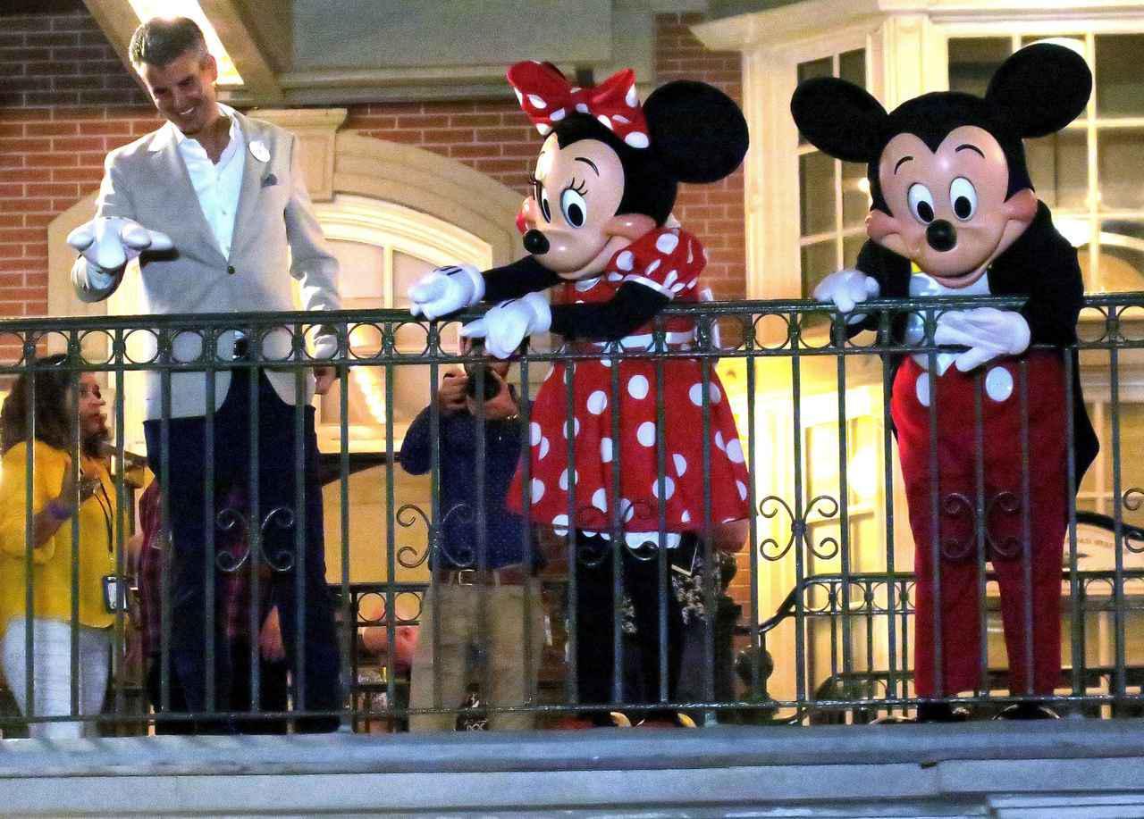 画像: 臨時休園前にミッキーマウス&ミニーマウスと一緒に、バルコニーからゲストに向かって手を振って挨拶をするダマロ氏。
