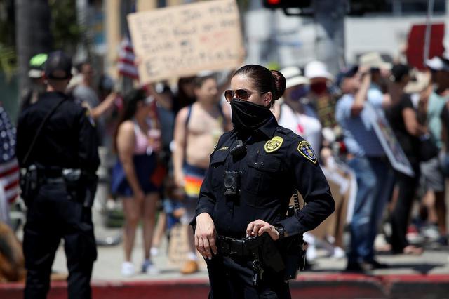 画像: カリフォルニア州サンディエゴで、デモを見守る警察官。(2020年4月26日に撮影)