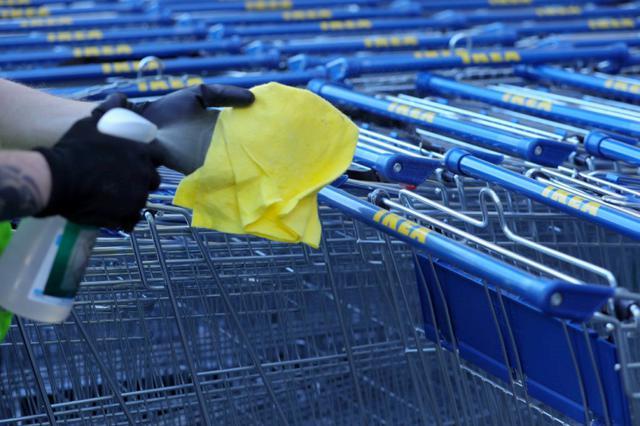 画像: ドイツ・コロンにあるイケアの店舗で除菌スプレーを使ってショッピングカートを清掃するスタッフ。
