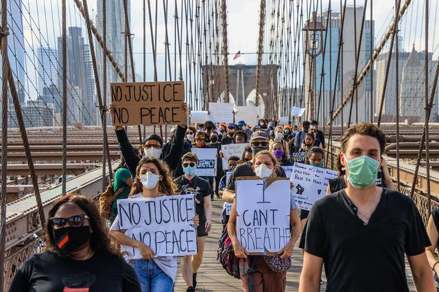 画像: プラカードを持ち、ニューヨークのブルックリン・ブリッジを占拠する人々。(5月30日撮影)