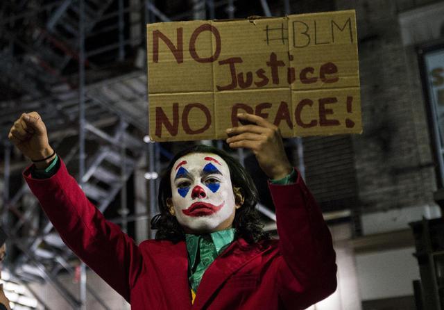 画像: 抗議デモにジョーカーの姿で参加した市民。(2020年5月31日にマサチューセッツ州のボストンで撮影)