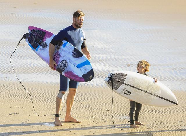 画像: 自宅近くのビーチで息子とサーフィンを楽しむクリス・ヘムズワース。