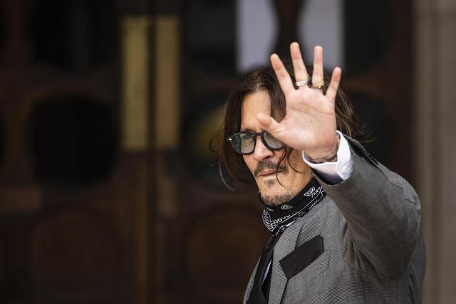 画像: 英現地時間7月13日、裁判所の前で集まった人たちに手を振って挨拶をするジョニー・デップ。