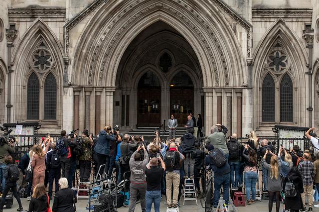 画像: 高等法院前で取材陣に囲まれるジョニー。