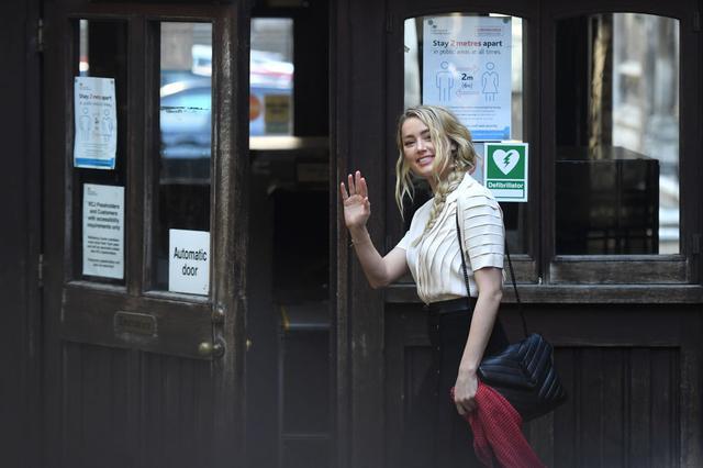 画像: 7月20日、笑顔で高等法院に入っていくアンバー。