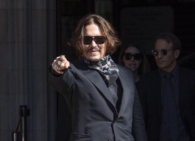 画像: 7月20日、高等法院前に集まった群衆を指さし、微笑むジョニー。