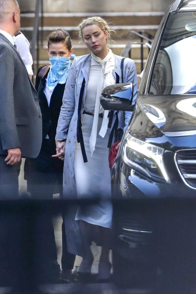 画像: 7月21日、証言2日目にロンドンの高等法院から現在の恋人と手を繋いで出てきたアンバー。
