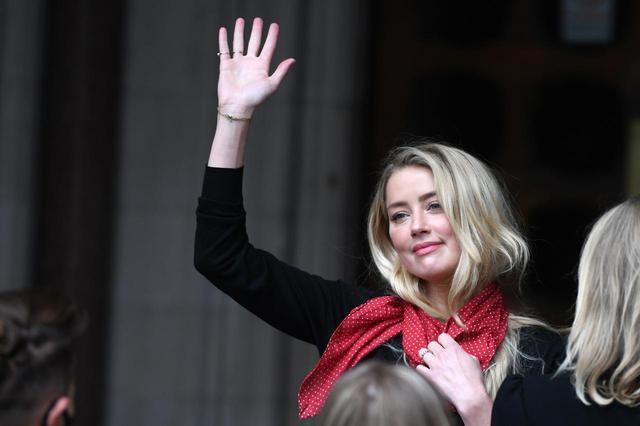 画像: 7月8日、高等法院前に集まった報道陣やファンに向かって手を振るアンバー・ハード。