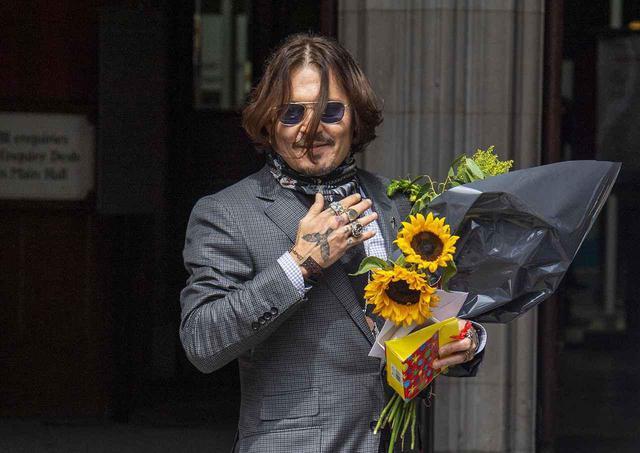 画像: 7月23日、高等法院前に集まったファンから花束やプレゼントを受け取ったジョニー・デップ。