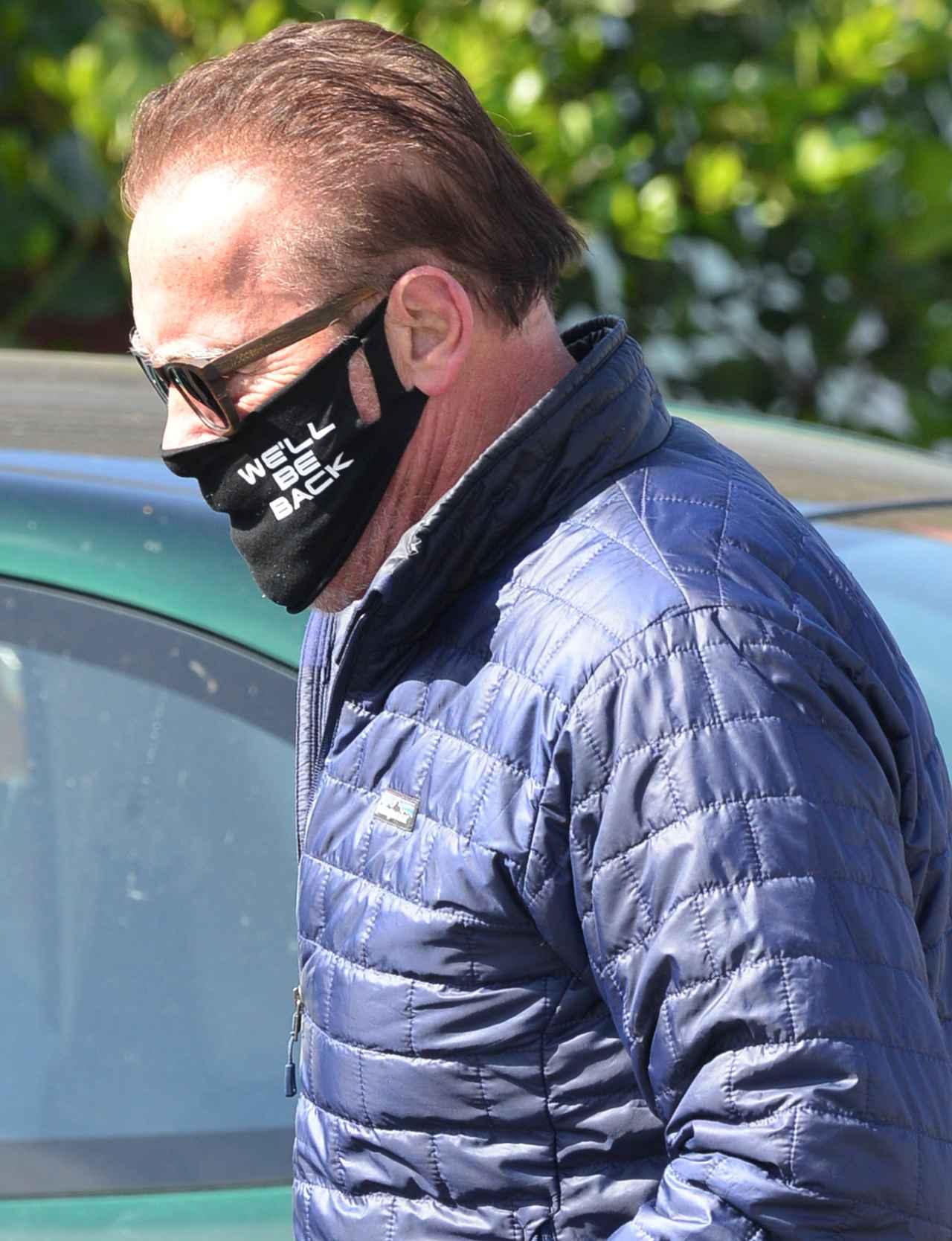 画像: 俳優のアーノルド・シュワルツェネッガーは、主演映画『ターミネーター』の台詞「I'll Be Back」をもじって「We'll Be Back(我々は帰ってくる)」と描かれたマスクを着けて外出。