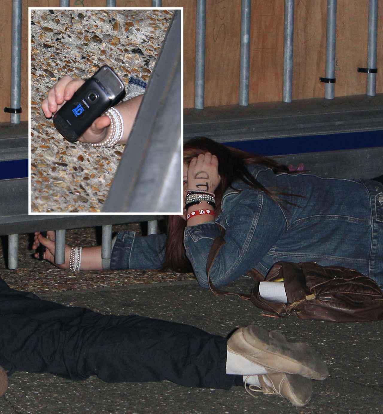 画像: リハーサル会場の中にいる1Dメンバーを撮ろうと地べたに寝転ぶファンたち。