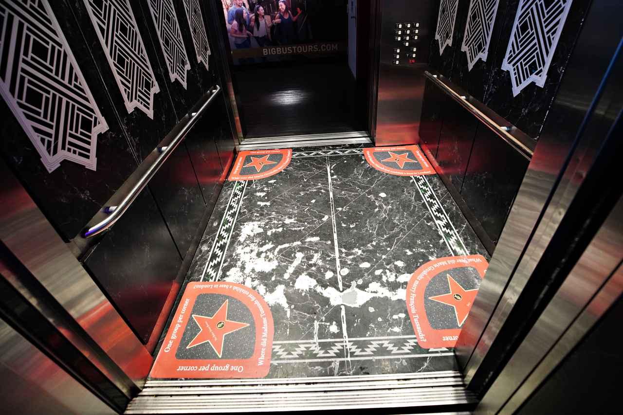 画像: エレベーターの床には、4つの角に「1コーナーに1グループずつ」と書かれた星のデザインを導入。