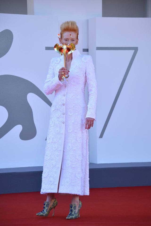 画像: ヴェネツィア国際映画祭にて、仮面舞踏会風のゴールドのマスクを持ってフォトコールに応じるティルダ。