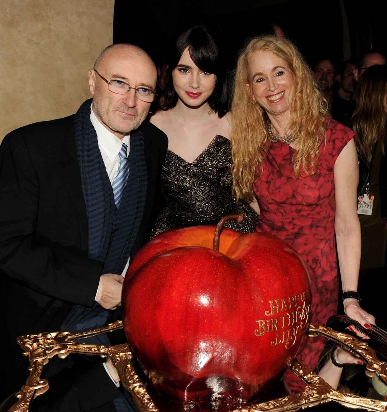 画像: 2012年、映画『白雪姫と鏡の女王』のプレミアのアフターパーティーで顔を揃えた父親フィル、リリー、母親ジル。