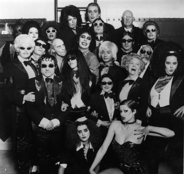 画像: 映画『ロッキー・ホラー・ショー』キャストの集合写真。画像中央で濃いアイメイクが特徴的な人物がティム・カリー