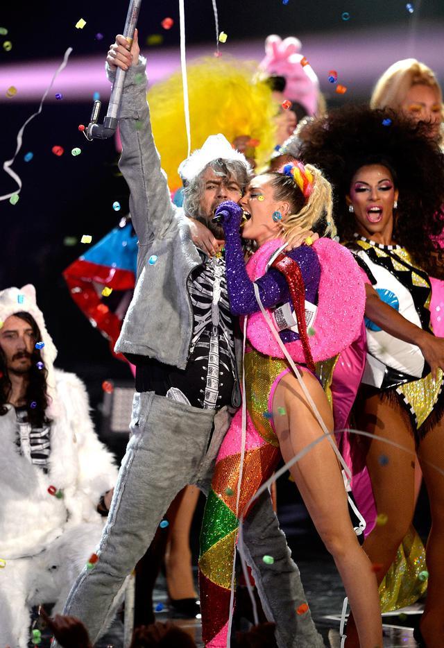 画像: 2015年のMTVビデオ・ミュージック・ビデオ・アワードでのマイリー・サイラスとコラボパフォーマンスを行なったザ・フレーミング・リップスのボーカル、ウェイン・コイン。