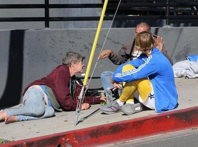 画像: コンビニの前で出会った男女のホームレスに水や食料を恵んであげただけでなく、地べたに座って話をするジャスティン。