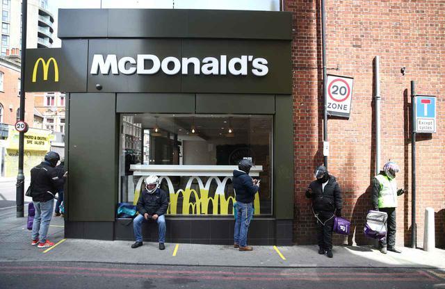 画像: マクドナルドで商品受け取りを待つデリバリー配達員。