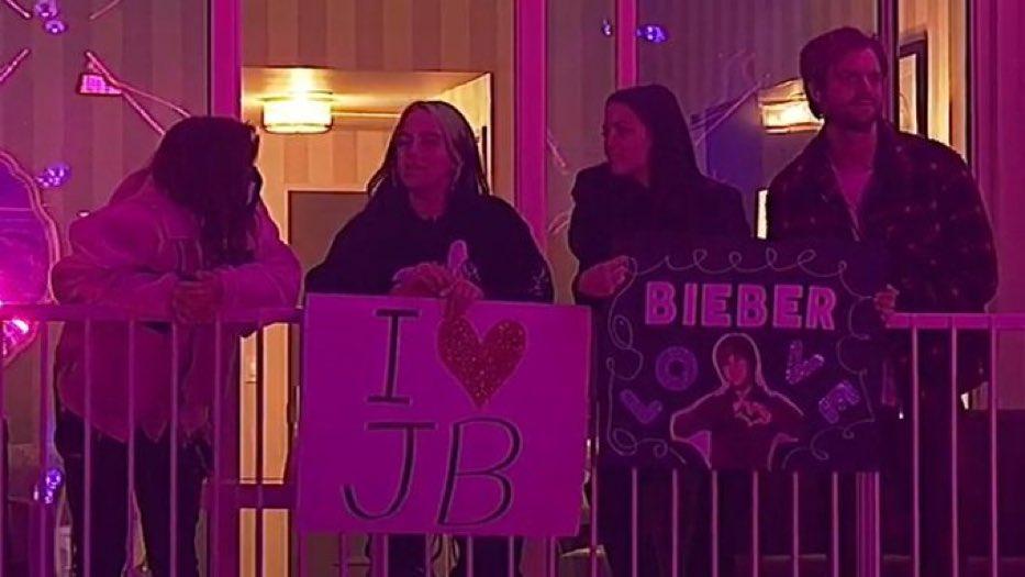 画像: ホテルの一室から「アイ・ラヴ・ジャスティン・ビーバー」と書かれたプラカードを持ってコンサートを生鑑賞するビリー・アイリッシュ(中央左)。