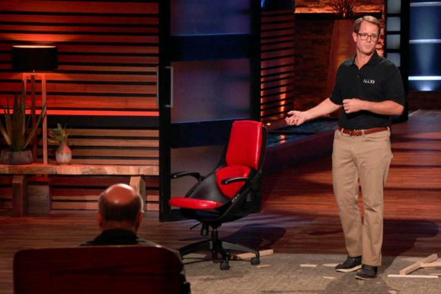 画像: サメ(投資家)たちの前で、ジャスティンが座っていたオフィスチェアを紹介するハウエンシュタイン氏。
