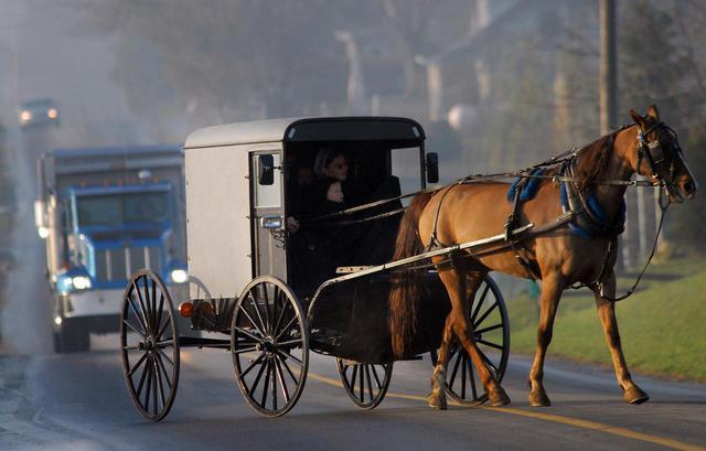 画像: ペンシルバニア州ランカスターで馬車で移動するアーミッシュの人々。