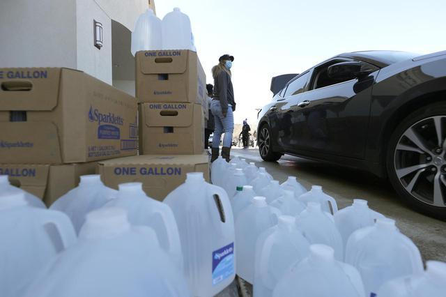 画像: 水を準備するボランティアたち。(2021年2月20日にテキサス州ヒューストンで撮影)