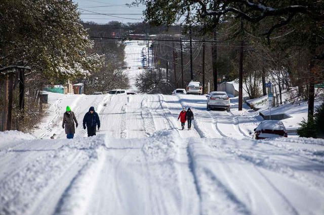 画像: 雪が積もった街を歩く人々。(2021年2月15日にテキサス州オースティンで撮影)