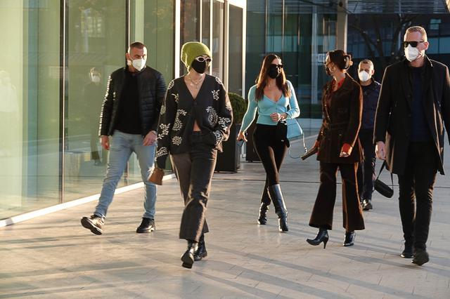 画像: ミラノ市内を移動中のジジたち。1人につき1人ずつボディガードらしき屈強な男性がついているのが印象的。柄カーディガンにグリーンのニット帽がジジ、ブルーのトップスがイリーナ、パンツスーツがベラ。