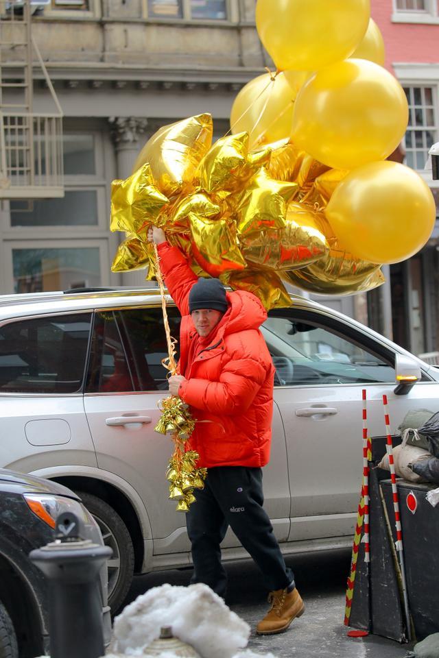 画像: 2月15日、ベビーシャワーが行なわれたニューヨーク市内の会場を大量の風船を持って後にするエミリーとセバスチャン。バルーンの色もジェンダーを限定しないゴールドとイエローで統一されていた。
